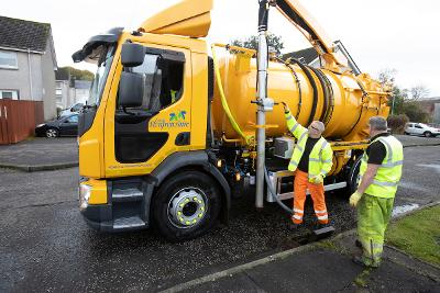 Roads workers unblocking drain